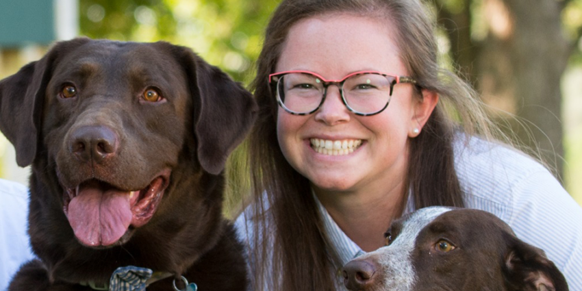 An image of a woman and her two dogs; Mallory Boyle, Paralegal from Acelity