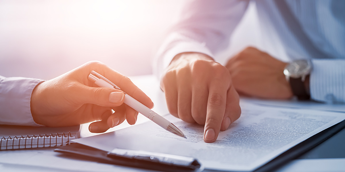 two people's hands pointing to a contract on a table