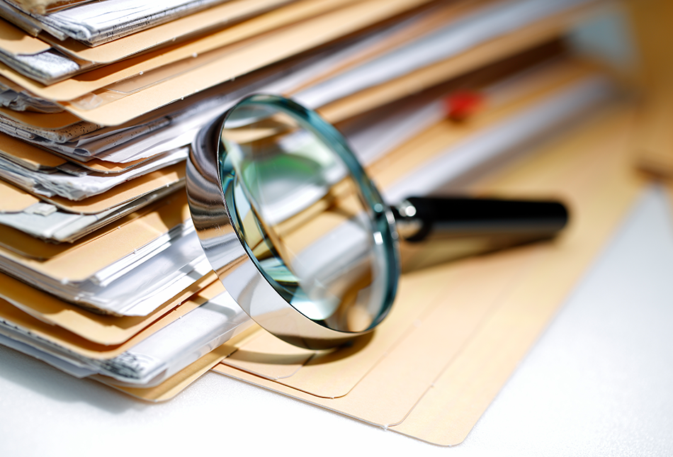Magnifying glass leaning against a large stack of full file folders