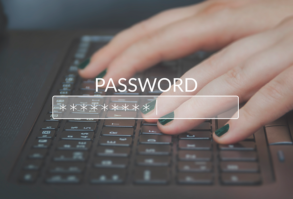 Hands typing in a password on a keyboard with painted nails