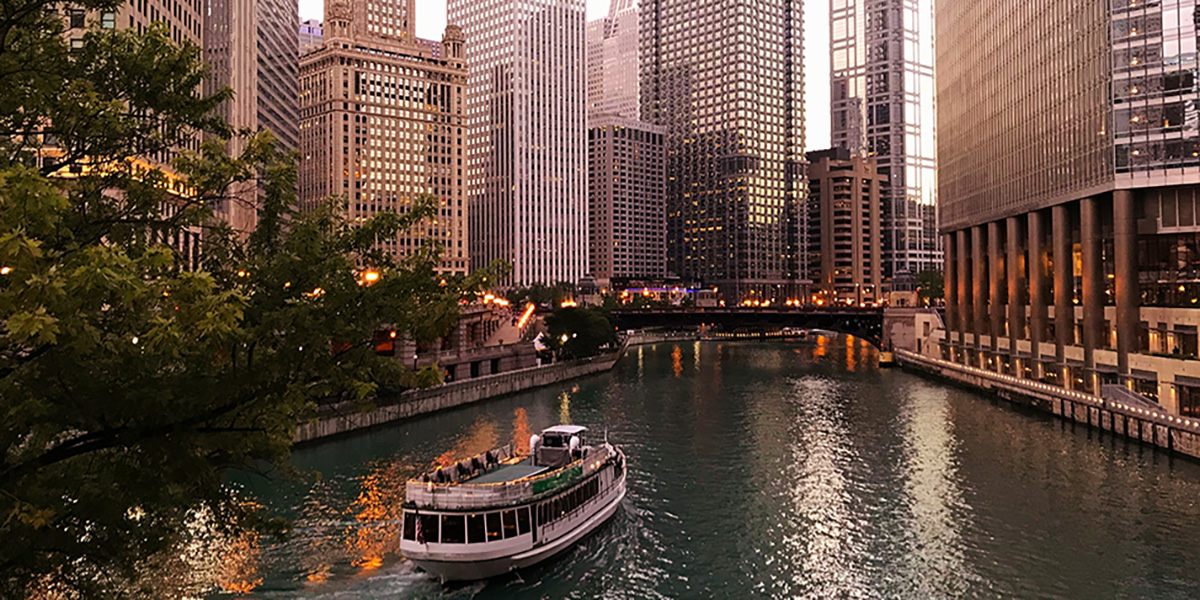 Riverboat in downtown Chicago at dusk - Things to do in Chicago as a PREX 2019 Attendee