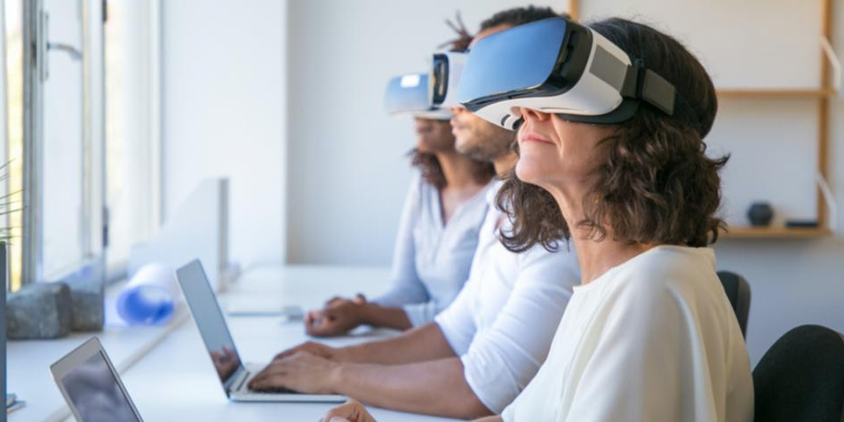 Two women and a man wearing VR headsets