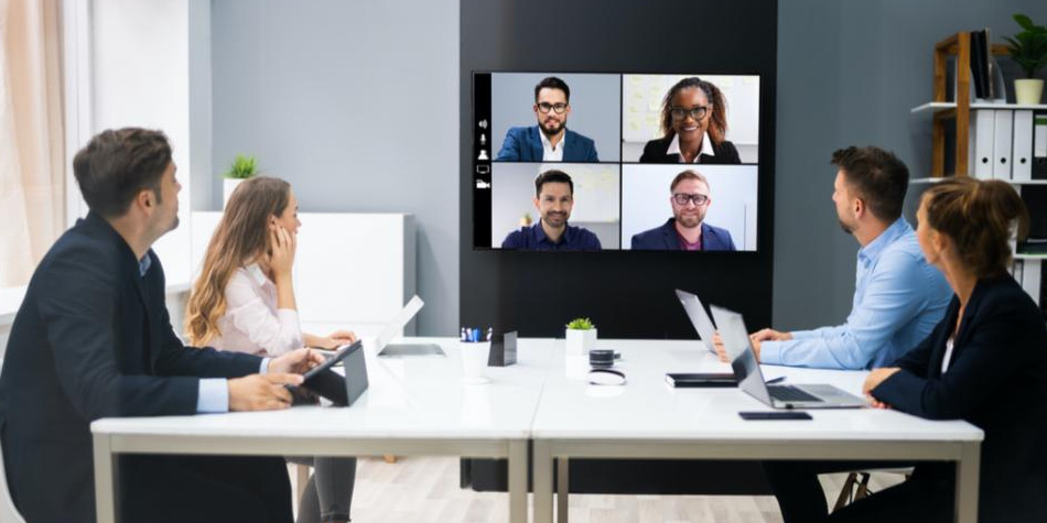 Group of people video conferencing with another