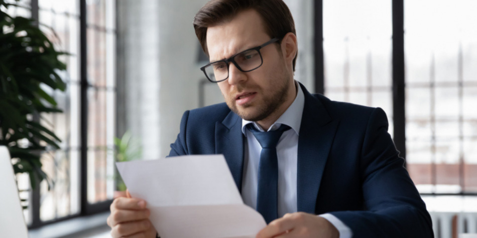 Man wearing glasses looking at contract