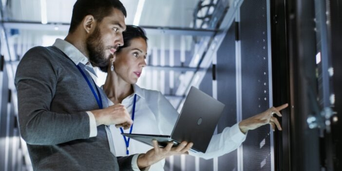 Woman and man with laptop in a server room