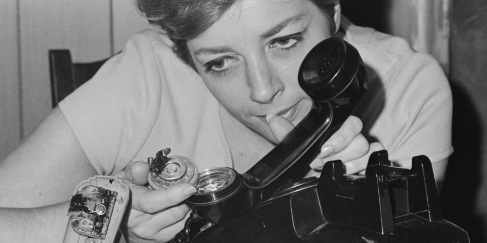 Woman looking at the insides of a phone from the 1960s