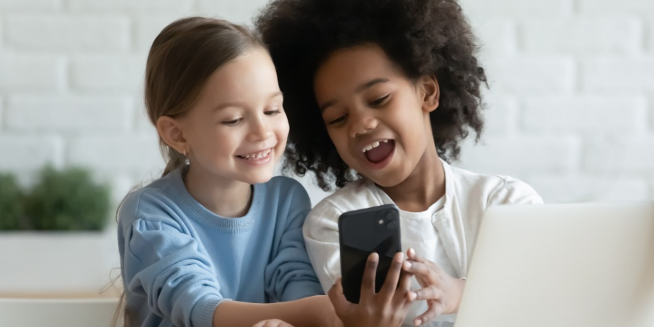 Two children looking at a mobile phone and laptop