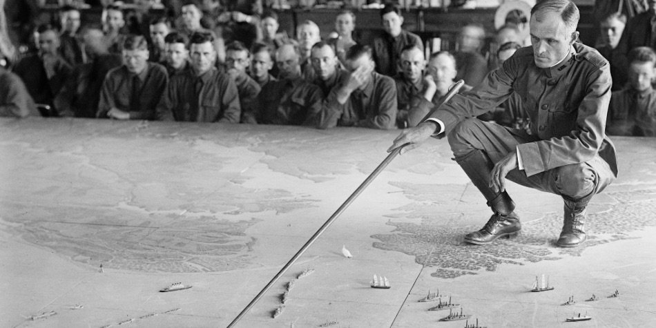 Man standing on map pushing military ships across the sea