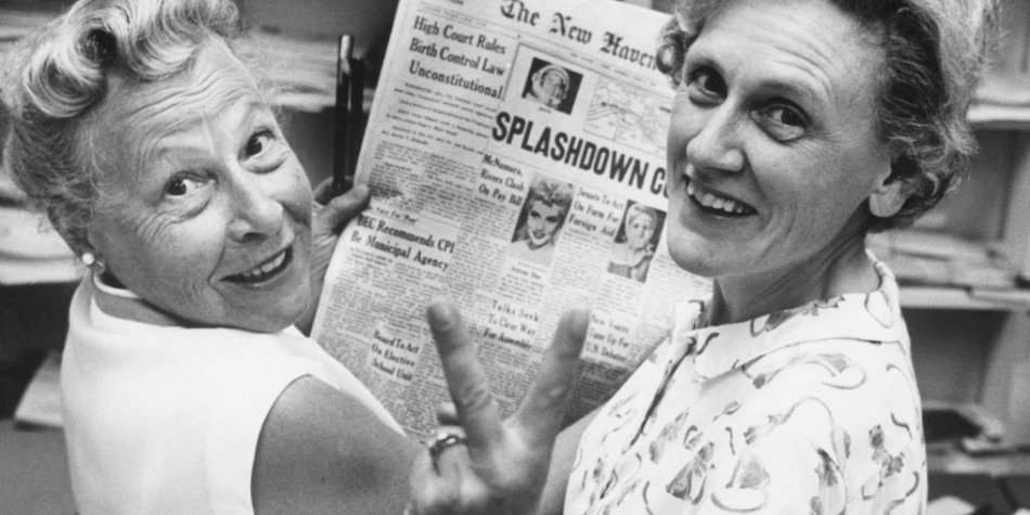 Two women from the 1960s reading a newspaper