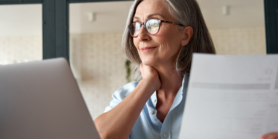 Woman with glasses looking at a report on a laptop