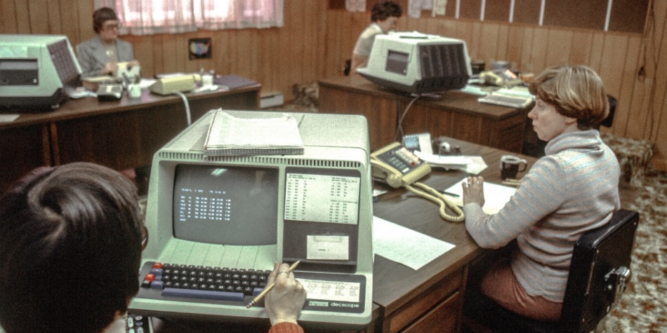 Several people in an office setting with large 1980s computers